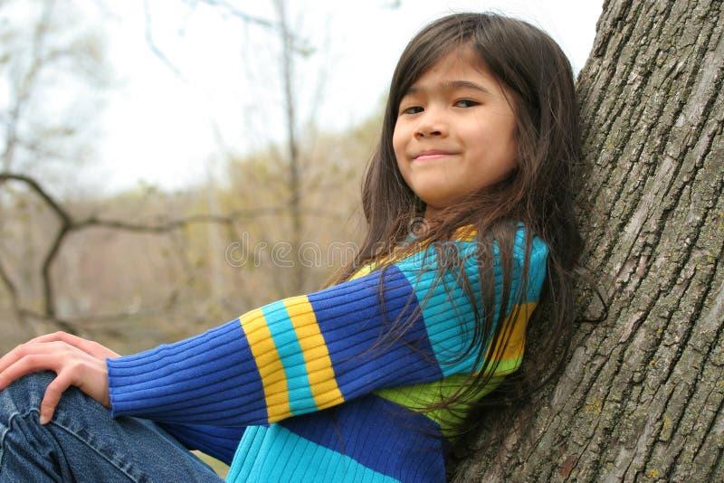 Uroczy małej dziewczynki obsiadanie w drzewie fotografia royalty free