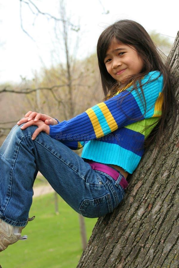 Uroczy małej dziewczynki obsiadanie w drzewie obraz stock
