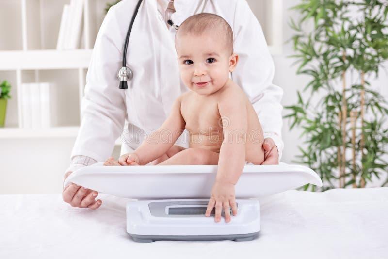 Uroczy mały dziecka dziecko z pediatra, obciąża mierzyć zdjęcie stock