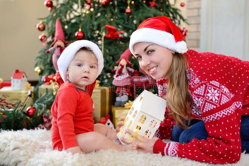 Uroczy mały dziecko i matka świętujemy boże narodzenia, patrzeje kamerę w Santa kapeluszy bawić się Nowego Roku ` s wakacje fotografia stock