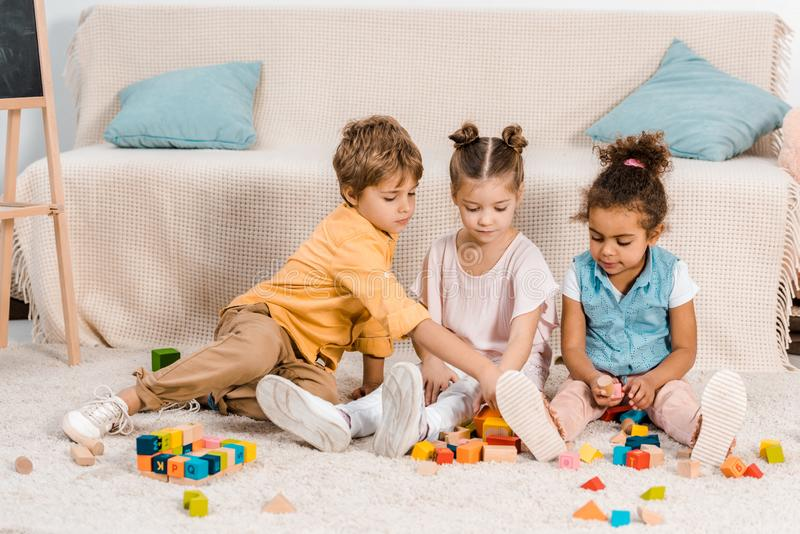 uroczy mali etniczni dzieci bawić się z kolorowymi sześcianami obraz stock