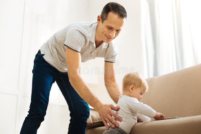 Uroczy miły ojciec pomaga jego dziecka stać blisko kanapy fotografia stock