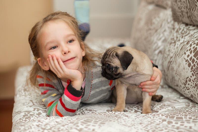Uroczy mopsa szczeniak bawić się z dziewczyną fotografia stock