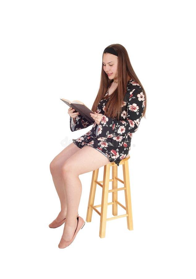 Uroczy nastoletniej dziewczyny obsiadanie, czytanie i książka obrazy royalty free