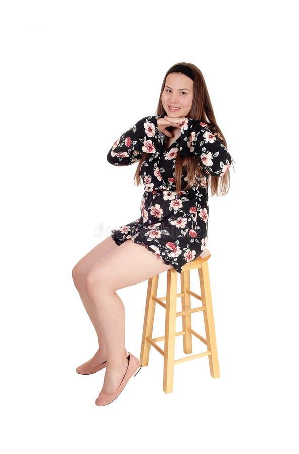 Uroczy nastoletniej dziewczyny obsiadanie na prętowym krześle, ono uśmiecha się obrazy stock