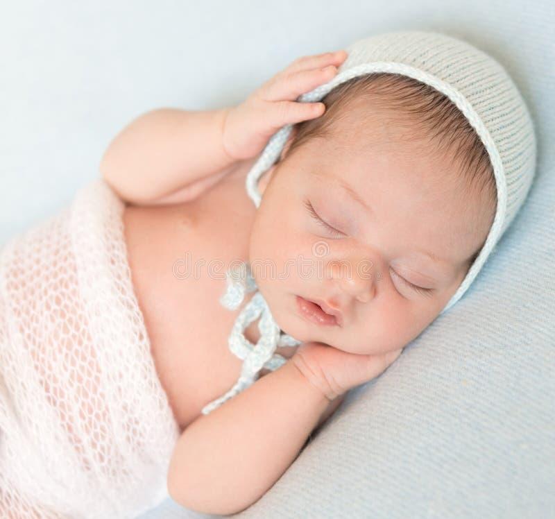 Uroczy nowonarodzony dziecka dosypianie z rękami na głowie zdjęcie stock