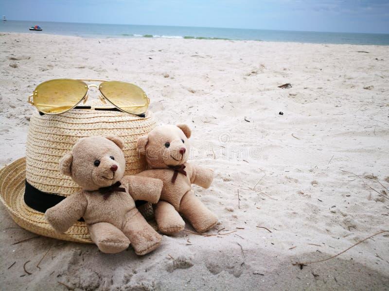 Uroczy para niedźwiedź na białej piasek plaży z szkłami przy Hua Hin plażą, rzeczy i akcesoriach dla kapeluszu i słońca, wakacje  zdjęcia stock