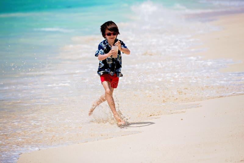 Uroczy preschool dzieci, chłopiec, mieć zabawę na ocean plaży Z podnieceniem dzieci bawić się z falami, dopłynięcie, chełbotanie  obraz stock