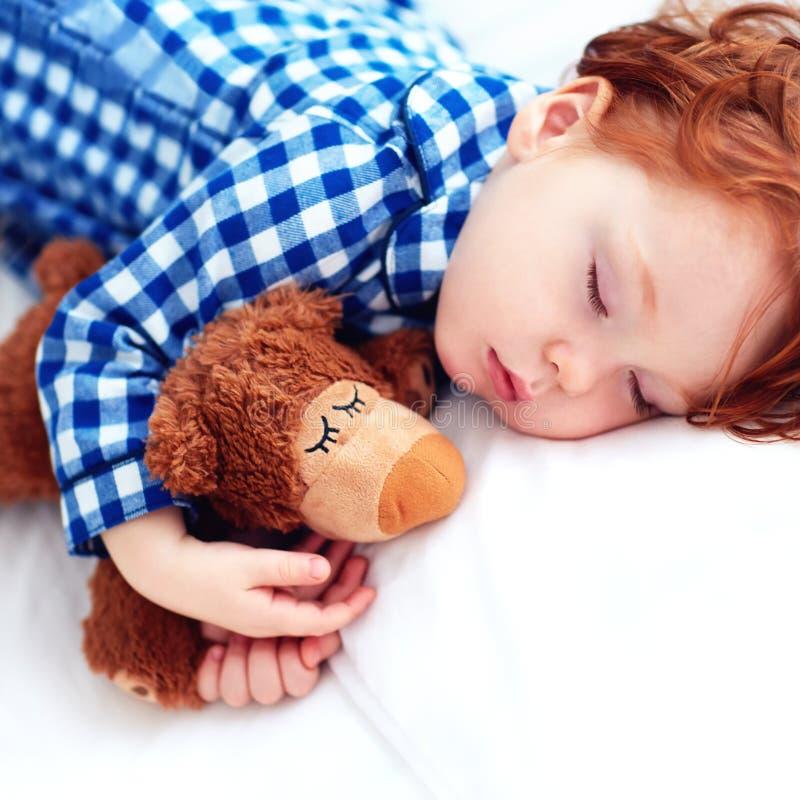 Uroczy rudzielec berbecia dziecka dosypianie z mokiet zabawką w flanelowych piżamach fotografia stock