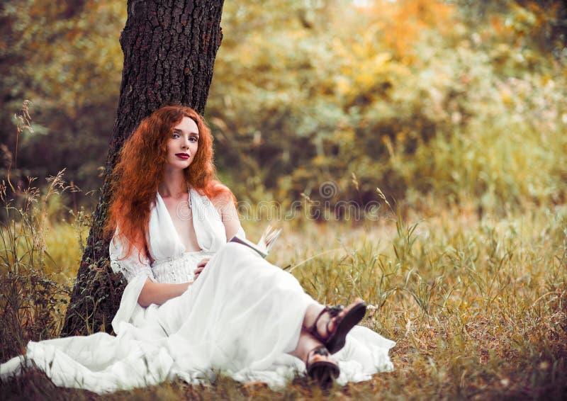 Uroczy rudzielec kobiety obsiadanie pod drzewem i czytaniem książka fotografia royalty free
