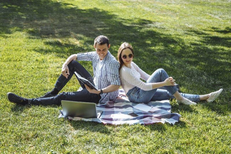 Uroczy studenci uniwersytetu studiuje outdoors w parku obraz stock