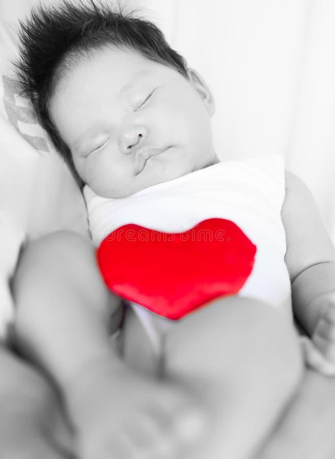 Uroczy sypialny dziecko jest kołysany matką w czarny i biały, podczas gdy trzymający odosobnionego czerwonego serce fotografia royalty free