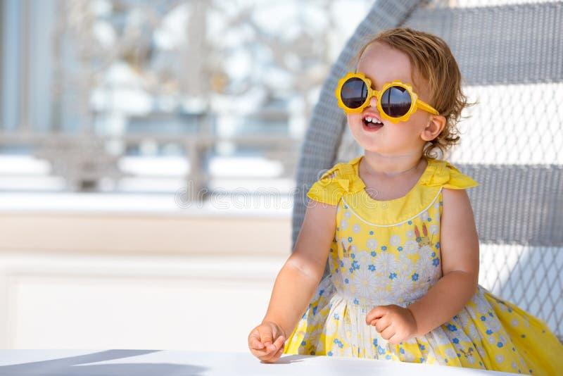 Uroczy szcz??liwy blondynka berbecia dziewczyny obsiadanie w plenerowej kawiarni zdjęcia royalty free