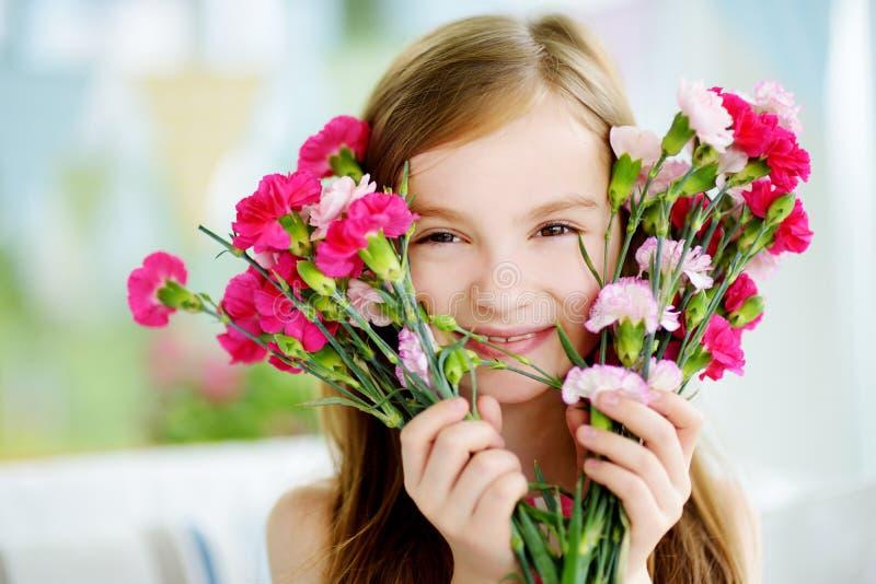 Uroczy uśmiechnięty małej dziewczynki mienie kwitnie dla jej mamy fotografia stock
