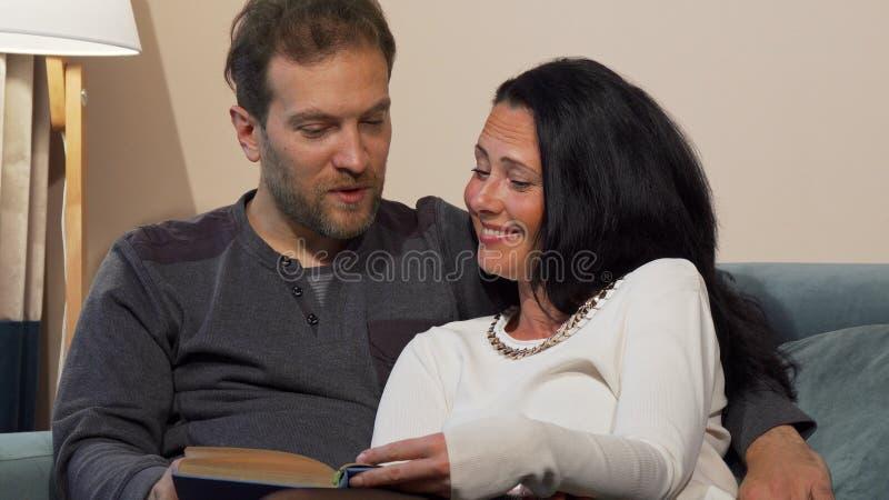 Uroczy zamężny dorośleć pary śmia się podczas gdy czytający książkę wpólnie obrazy stock