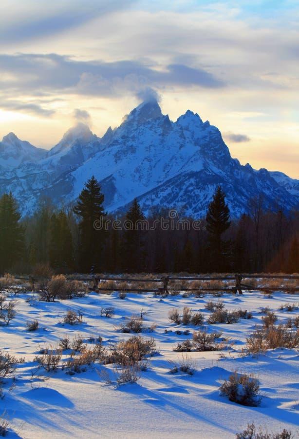 Uroczysty Tetons sztachetowego ogrodzenia rozszczepiony widok przy alpenglow mrocznym zmierzchem pod soczewkowatymi chmurami w Ur obraz royalty free