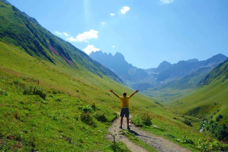 Uroczysty wysokogórski pasmo górskie z młodym człowiekiem prowadzi od Juty Chaukhi przepustka na wycieczkuje śladzie, Kaukaz góry fotografia stock