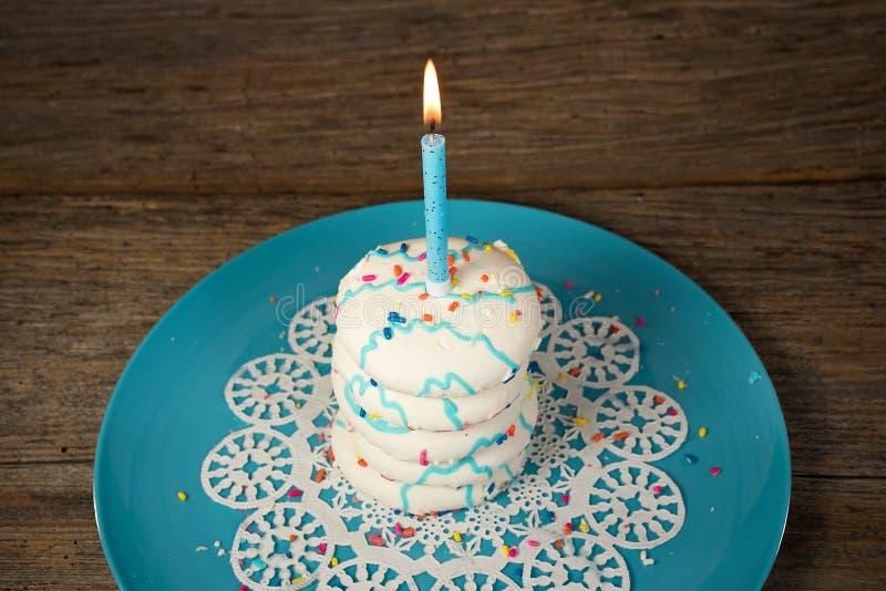 Urodzinowa świeczka na cukrowego ciastka stercie obrazy stock