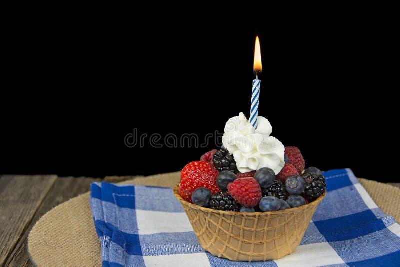 Urodzinowa świeczka w jagodowym pucharze fotografia stock
