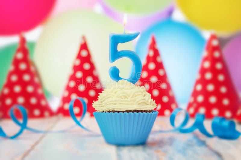 Urodzinowa świeczka w kształcie liczba w babeczce obrazy stock