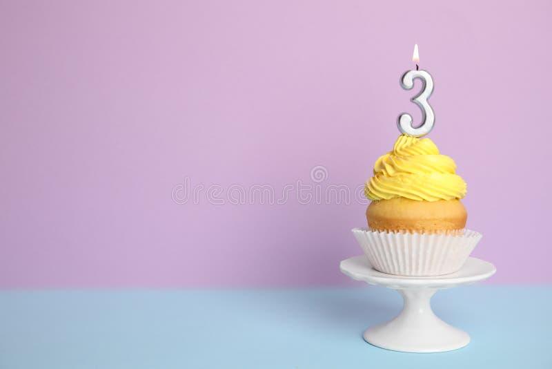 Urodzinowa babeczka z liczbą trzy świeczki dalej przeciw koloru tłu, przestrzeń dla teksta obrazy stock