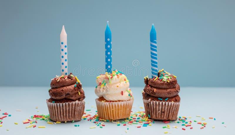 Urodzinowe babeczki z świeczkami na błękitnym pastelowym tle, kopii przestrzeń fotografia royalty free