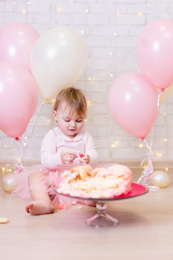 Urodzinowy świętowanie śmieszny małej dziewczynki łasowanie i niszczący cak - zdjęcia stock