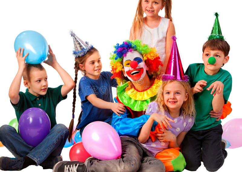 Urodzinowy błazen bawić się dzieci Dzieciak jest ubranym partyjnych kapeluszowych chwytów balony zdjęcia stock