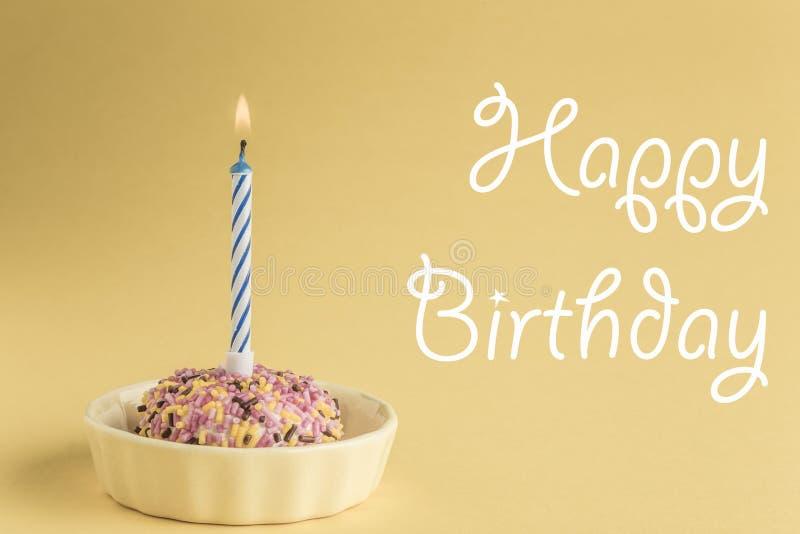 Urodzinowy tort z jeden świeczką na kolorze żółtym fotografia stock