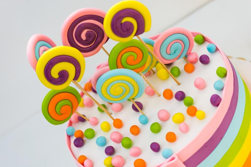 Urodzinowy tort z kolorowymi lizakami na białym tle zdjęcia stock