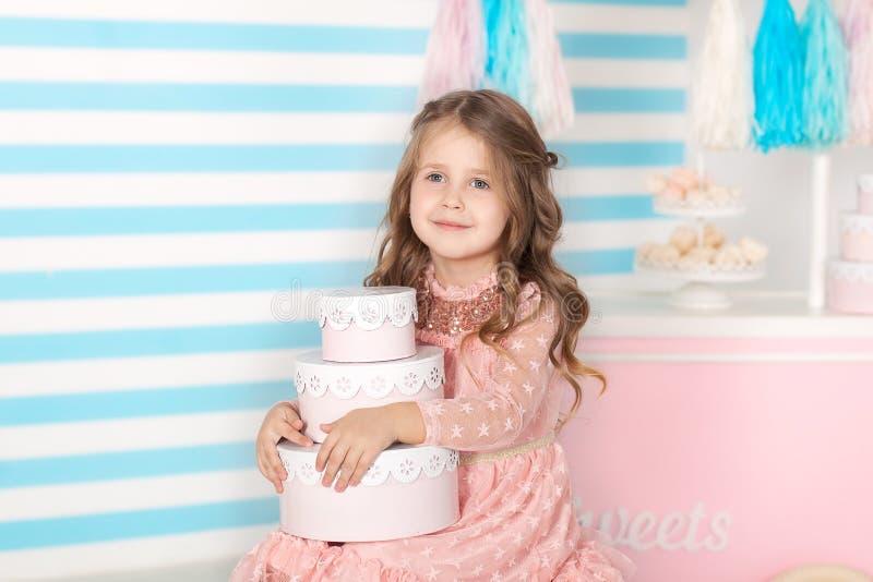 Urodziny! Piękny małej dziewczynki obsiadanie z prezentami Cukierku urodziny bar Portret dziecko twarzy zbliżenie Mały śliczny dz fotografia royalty free