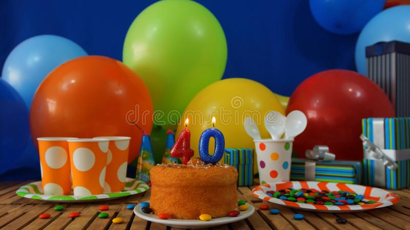 Urodziny 40 tort na nieociosanym drewnianym stole z tłem kolorowi balony, prezenty, plastikowe filiżanki, klingerytu talerz fotografia royalty free