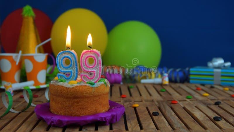 Urodziny 99 tort z świeczkami na nieociosanym drewnianym stole z tłem kolorowi balony, prezenty, plastikowe filiżanki i cukierki, zdjęcia royalty free