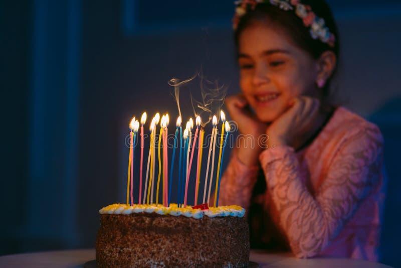 Urodziny Troszkę dmucha za świeczkach na podsycającym słodka dziewczyna obraz stock