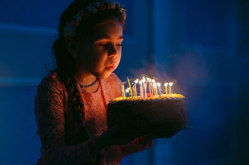 Urodziny Troszkę dmucha za świeczkach na podsycającym słodka dziewczyna obrazy royalty free