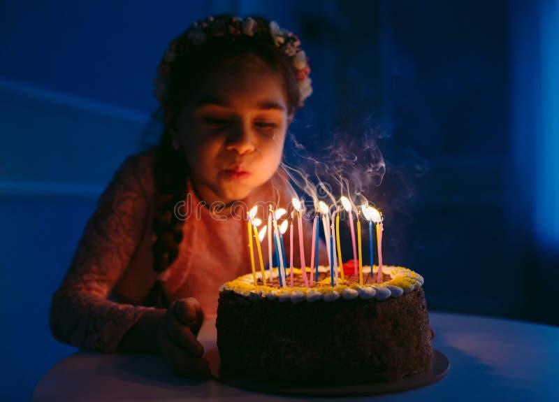 Urodziny Troszkę dmucha za świeczkach na podsycającym słodka dziewczyna zdjęcie stock
