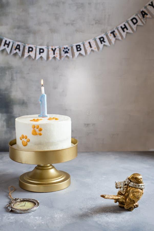 Urodziny zwierząt domowych Ciasto świąteczne z odciskami łapy i świecą na szarym tle Kopiuj miejsce Piekarnia, słodycze, koncepcj obraz stock