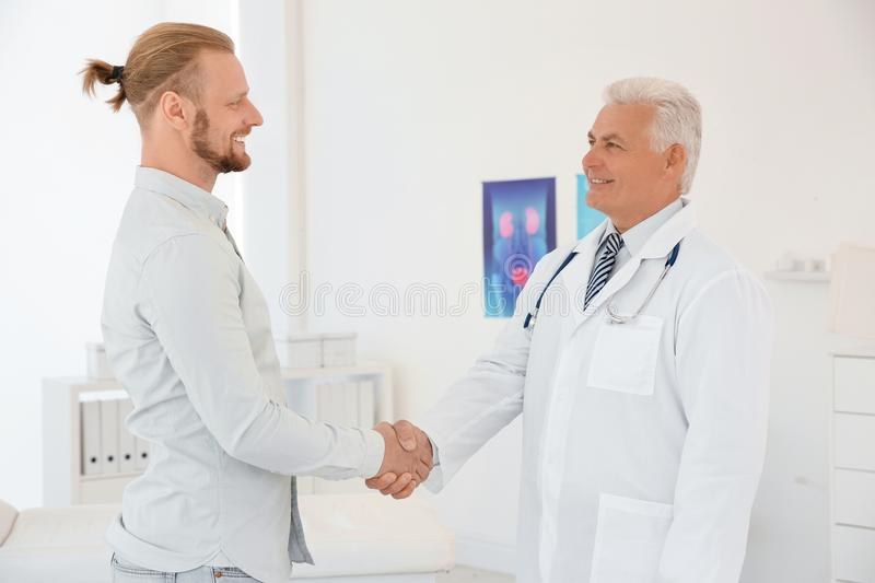 Urologist and thankful patient shaking hands stock images
