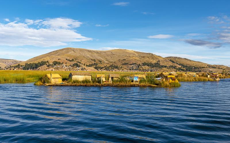 Uros Floating Islands in the Titicaca Lake, Peru. The floating totora reed islands of the Uros indigenous group on the blue waters of the Titicaca Lake near the royalty free stock image