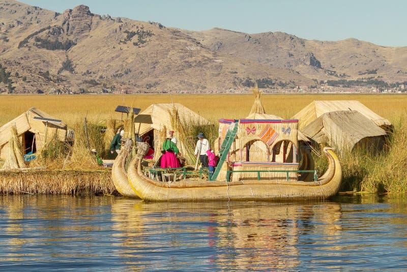 UROS, PERU - JULI 29 2012: Familie die op drijvend rieteiland Uros bij meer Titicaca Peru Bolivia leven stock foto