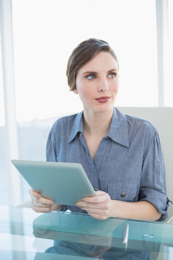 Ursnygg affärskvinna som rymmer hennes minnestavla, medan sitta på hennes skrivbord arkivbilder