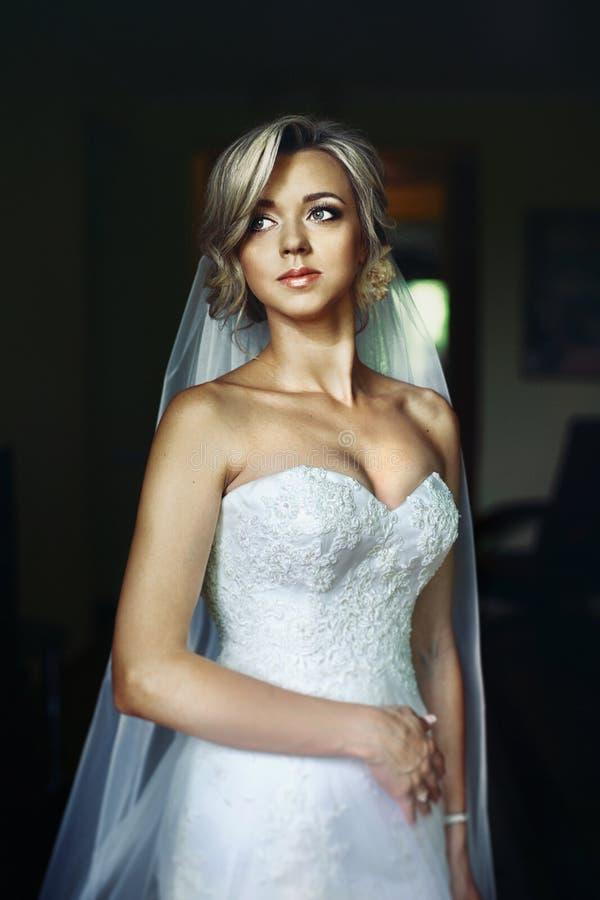 Ursnygg blond brud i den vita klänningen som poserar i hotellrum royaltyfri fotografi