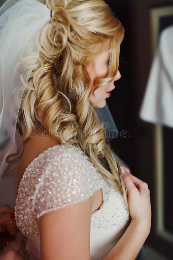 Ursnygg blond brud som poserar i den vita klänningen för tappning i hotellroo arkivfoto