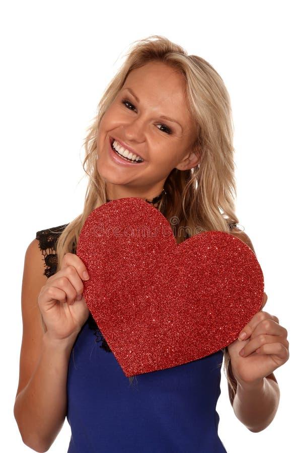 Ursnygg blond flicka med stor röd hjärta royaltyfri bild
