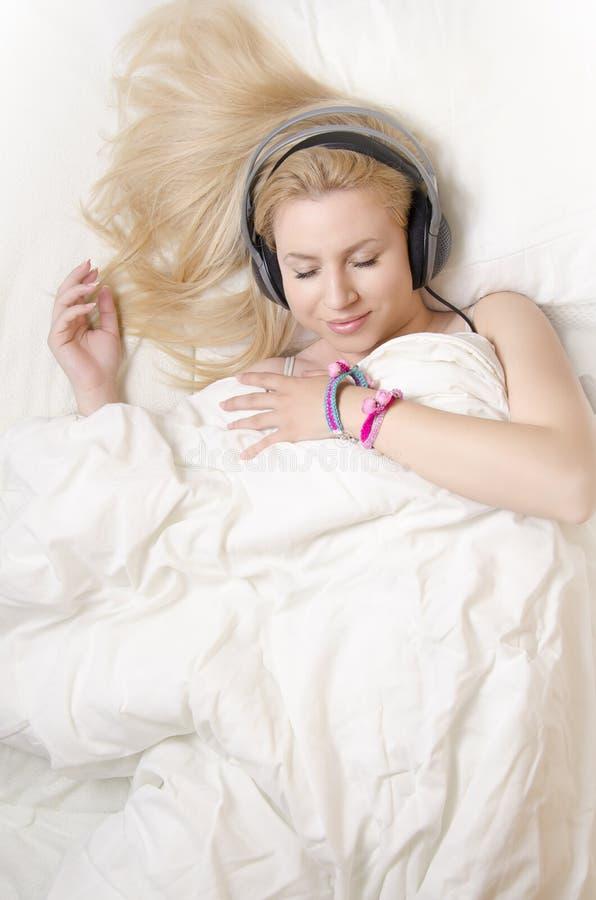 Ursnygg blond flicka som ligger i säng, lyssnande avkopplingmusik arkivbild