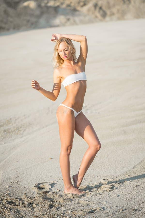 Ursnygg blond flickamodell med den perfekta kroppen som poserar på stranden fotografering för bildbyråer