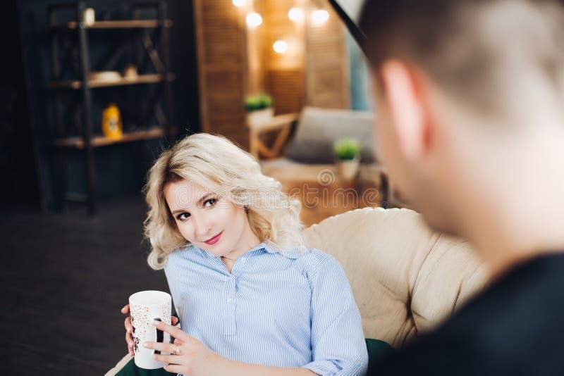 Ursnygg blond flickvän som sitter på lagledaren mot hennes boyfiend arkivbilder