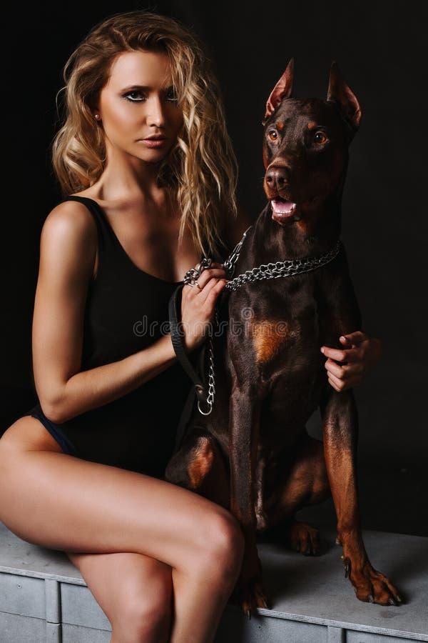 Ursnygg blond kvinna i en svart bodysuit med dobermanen som ser kameran Härlig flicka med länge garvade ben arkivfoto