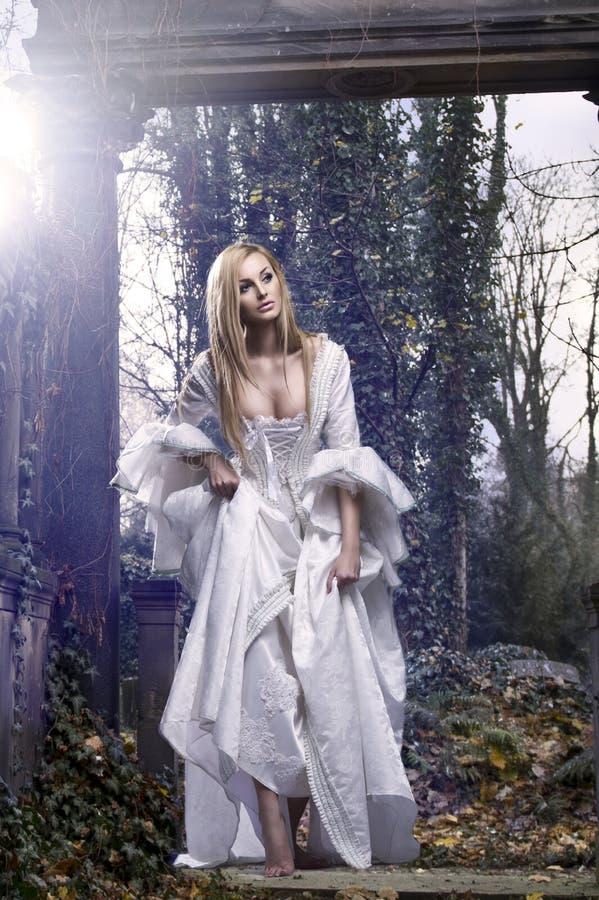 Ursnygg blond skönhet i en gammalmodig klänning royaltyfria foton