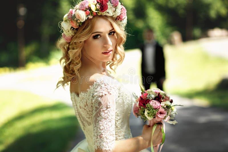 Ursnygg blondin som ler den emotionella bruden i vit klänning I för tappning royaltyfri foto